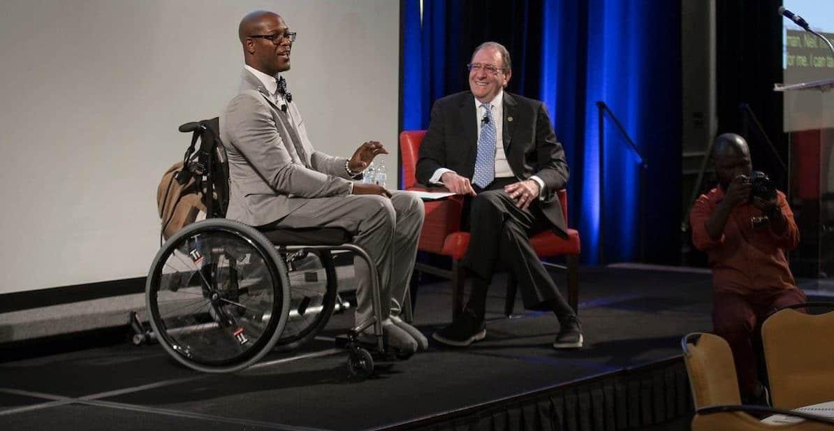 Man in wheelchair on stage in conversation
