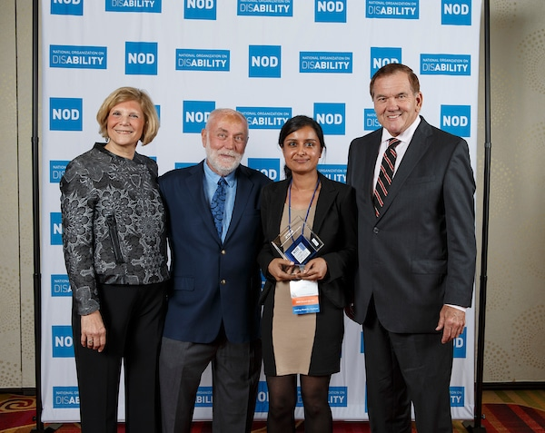 JetBlue's Sharn Kamal, posing with the 2018 Leading Disability Employer award, with Gov. Tom Ridge, actor Robert David Hall and NOD President Carol Glazer