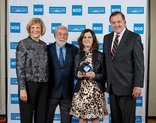 L'Oreal USA's Rebecca Caruso, posing with the 2018 Leading Disability Employer award, with Gov. Tom Ridge, actor Robert David Hall and NOD President Carol Glazer
