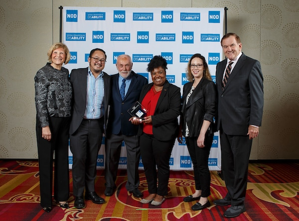 PwC's Jason Capili, Tamara Burks and Carrie Schroeder, posing with the 2018 Leading Disability Employer award, with Gov. Tom Ridge, actor Robert David Hall and NOD President Carol Glazer