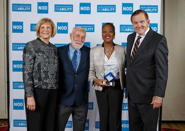Aetna's Djuana C. Beamon, posing with the 2018 Leading Disability Employer award, with Gov. Tom Ridge, actor Robert David Hall and NOD President Carol Glazer