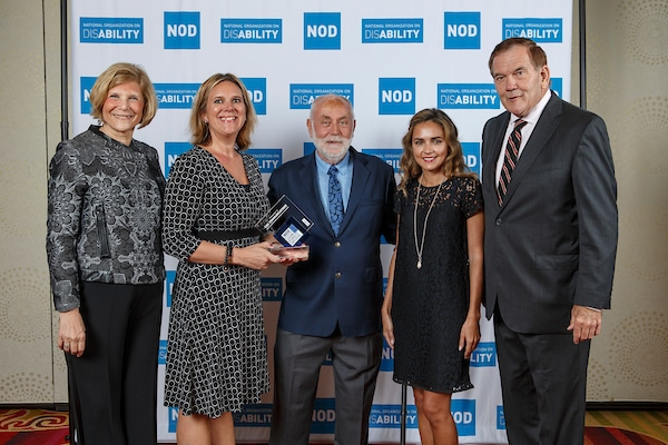 Cox Communications' Jennifer Cobb, posing with the 2018 Leading Disability Employer award, with Gov. Tom Ridge, actor Robert David Hall and NOD President Carol Glazer