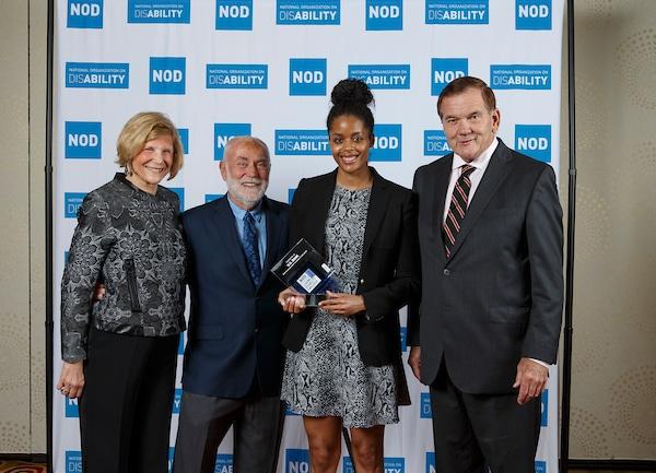 U.S. Bank's Nicole Taylor, posing with the 2018 Leading Disability Employer award, with Gov. Tom Ridge, actor Robert David Hall and NOD President Carol Glazer