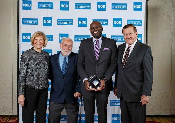 Procter and Gamble representative posing with the 2018 Leading Disability Employer award, with Gov. Tom Ridge, actor Robert David Hall and NOD President Carol Glazer