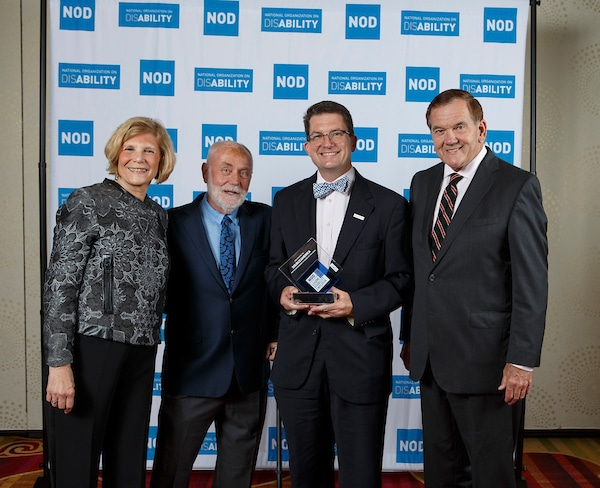 SourceAmerica representative, posing with the 2018 Leading Disability Employer award, with Gov. Tom Ridge, actor Robert David Hall and NOD President Carol Glazer
