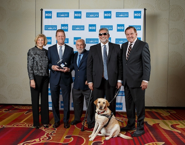 Eli Lilly & Co.'s Mark Dresen and Stephen Fry, posing with the 2018 Leading Disability Employer award, with Gov. Tom Ridge, actor Robert David Hall and NOD President Carol Glazer