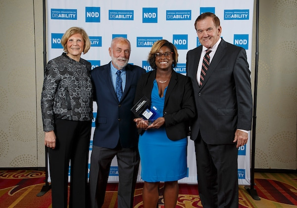 Lockheed Martin's Brooke Thomas, posing with the 2018 Leading Disability Employer award, with Gov. Tom Ridge, actor Robert David Hall and NOD President Carol Glazer