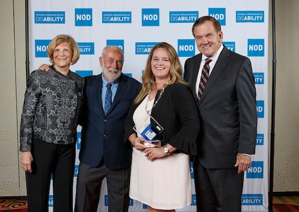 Merck's Cathy Carroll, posing with the 2018 Leading Disability Employer award, with Gov. Tom Ridge, actor Robert David Hall and NOD President Carol Glazer