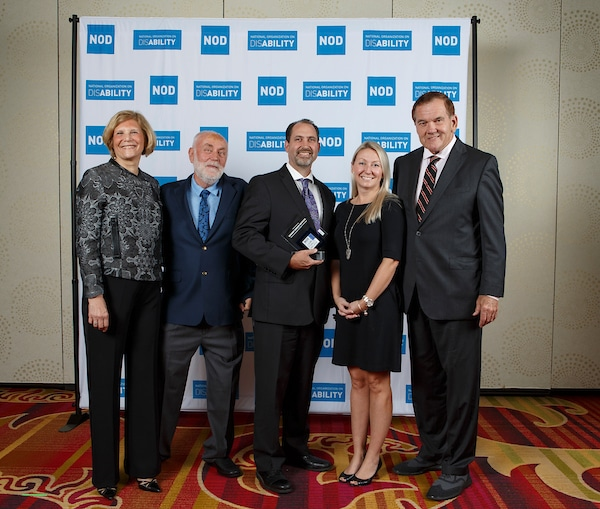 Kennedy Krieger Institute's Daniel Durgin and Tina Marie Schmitt, posing with the 2018 Leading Disability Employer award, with Gov. Tom Ridge, actor Robert David Hall and NOD President Carol Glazer