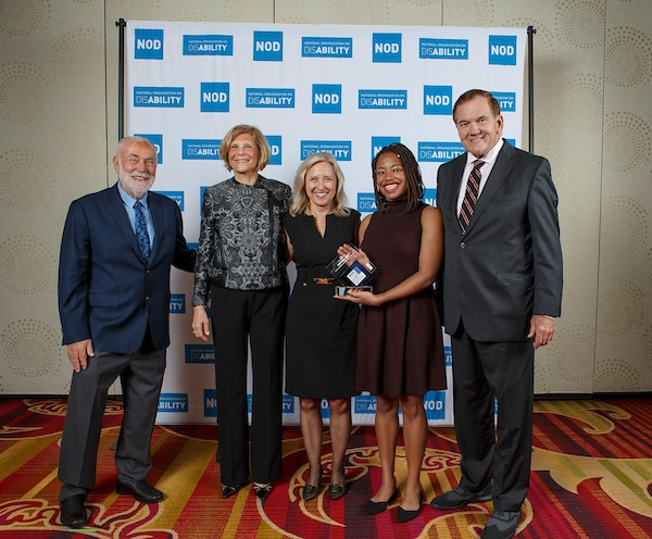 Capital One's Schuyler Atkins and Laura Bailey, , posing with the 2018 Leading Disability Employer award, with Gov. Tom Ridge, actor Robert David Hall and NOD President Carol Glazer