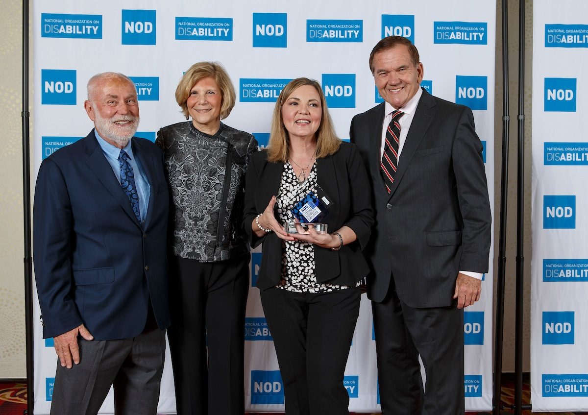 Southern California Edison's Raquel Morales, posing with the 2018 Leading Disability Employer award, with Gov. Tom Ridge, actor Robert David Hall and NOD President Carol Glazer