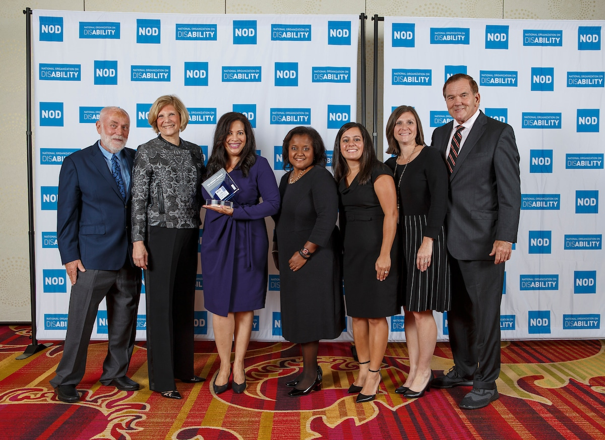 The Hershey Company's Victoria Zefran, Esther Read and Ipalla G. Cooke, posing with the 2018 Leading Disability Employer award, with Gov. Tom Ridge, actor Robert David Hall and NOD President Carol Glazer