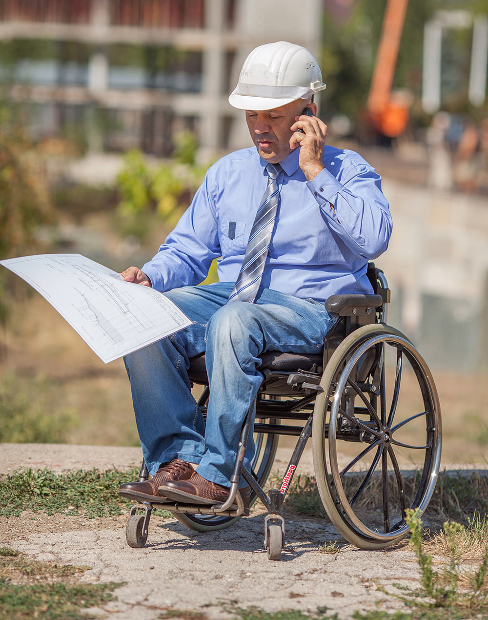 Male construction professional in a wheelchair, at a jobsite holding plans