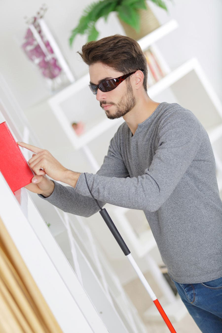Dark-haired Blind man wearing wraparound sunglasses, folding cane looped around his arm, stands at a bookshelf and inspects the spine of a braille book