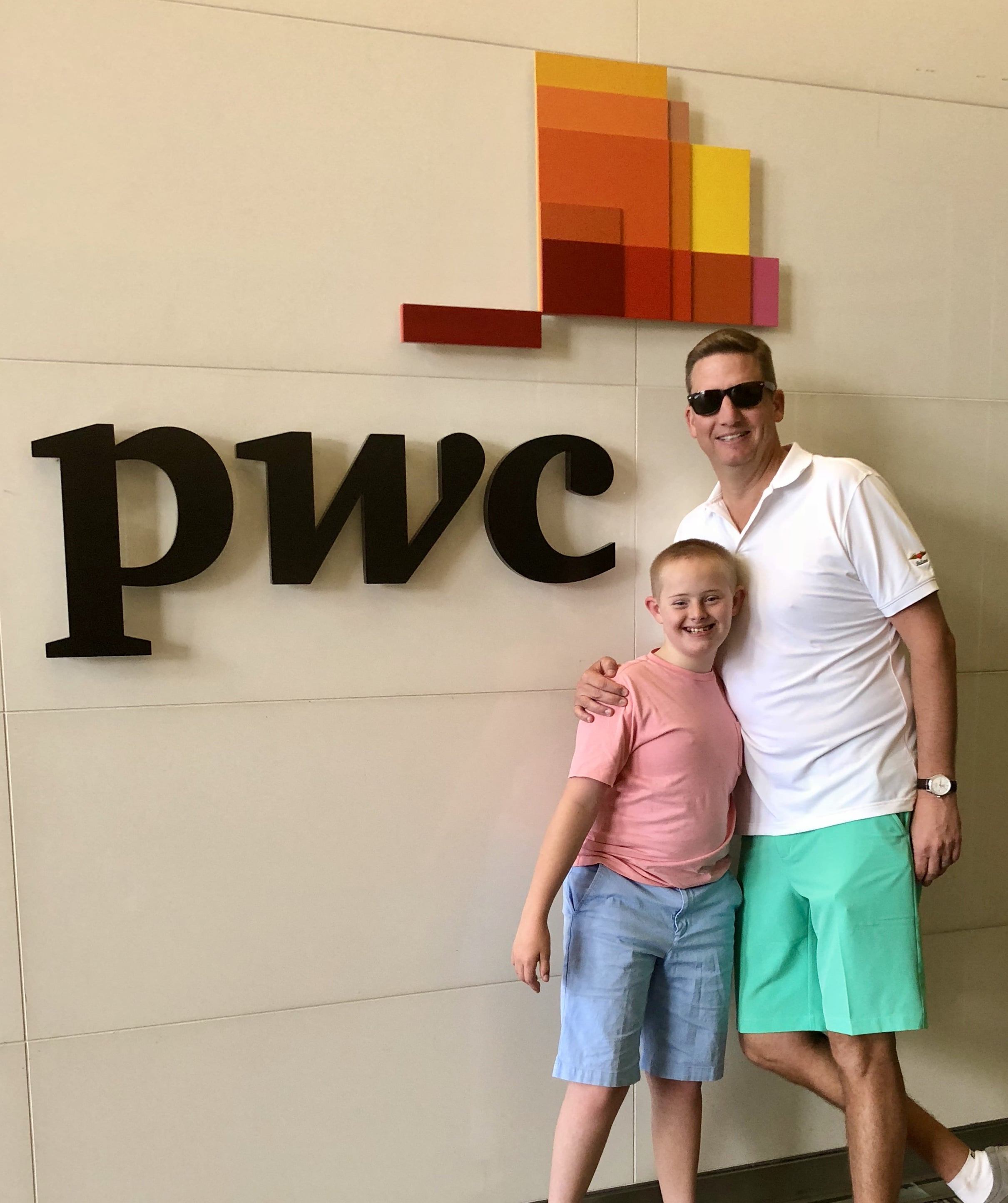 Brad Hopton and son Braden pose in front of PwC's London office