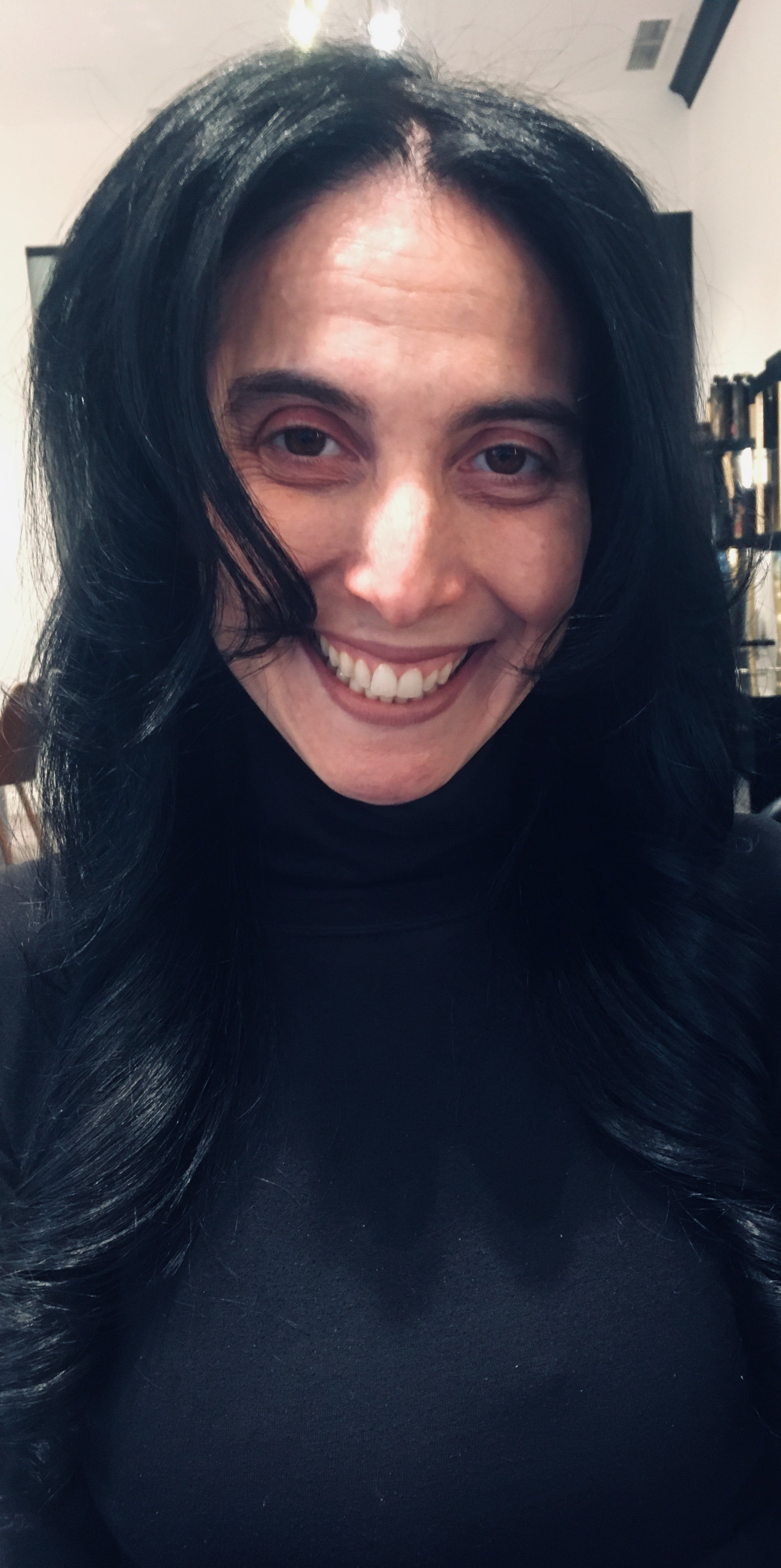 Head shot of Carolyn Cannistraro wearing black turtleneck smiling for camera