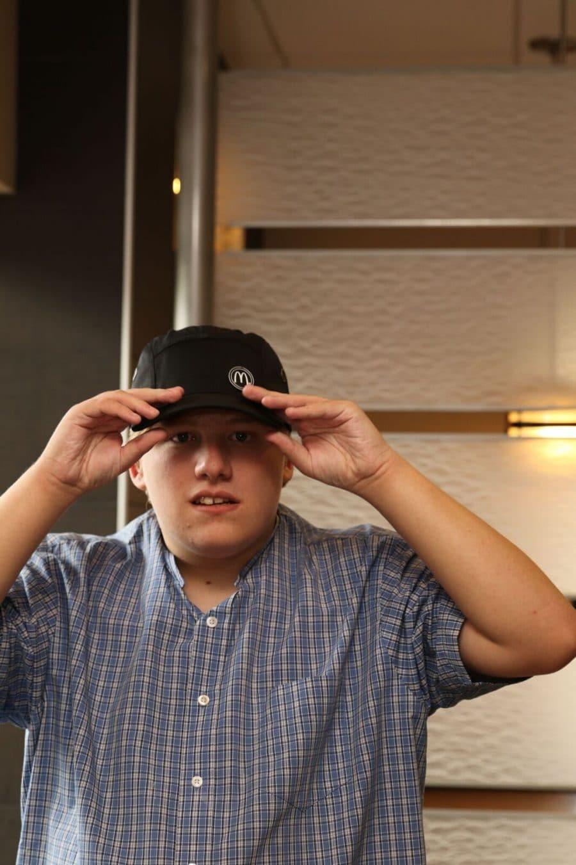 Photo of Carter Dodd proudly putting on his McDonald's crew-member cap.
