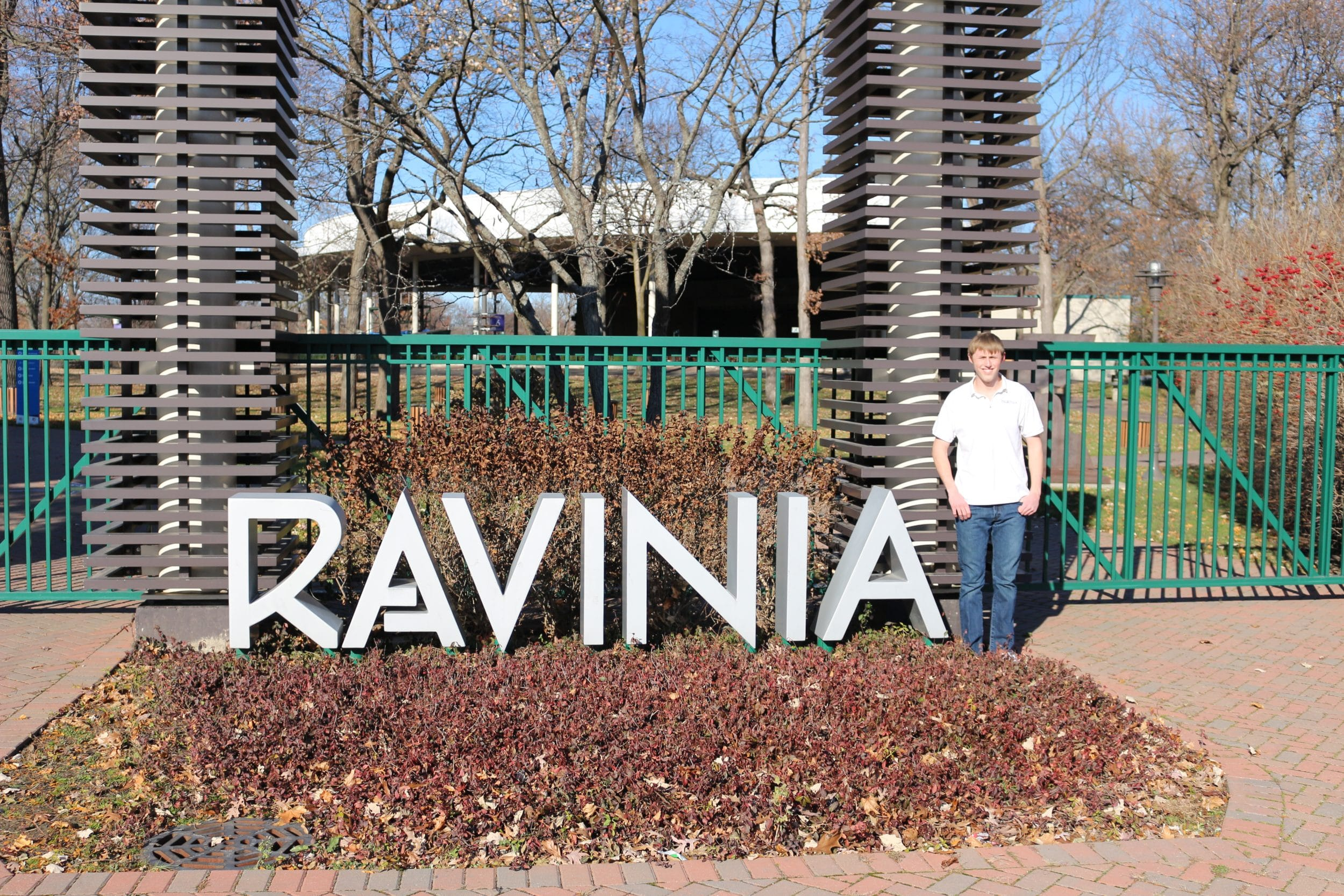 Cole Nelson standing beside Ravinia signage