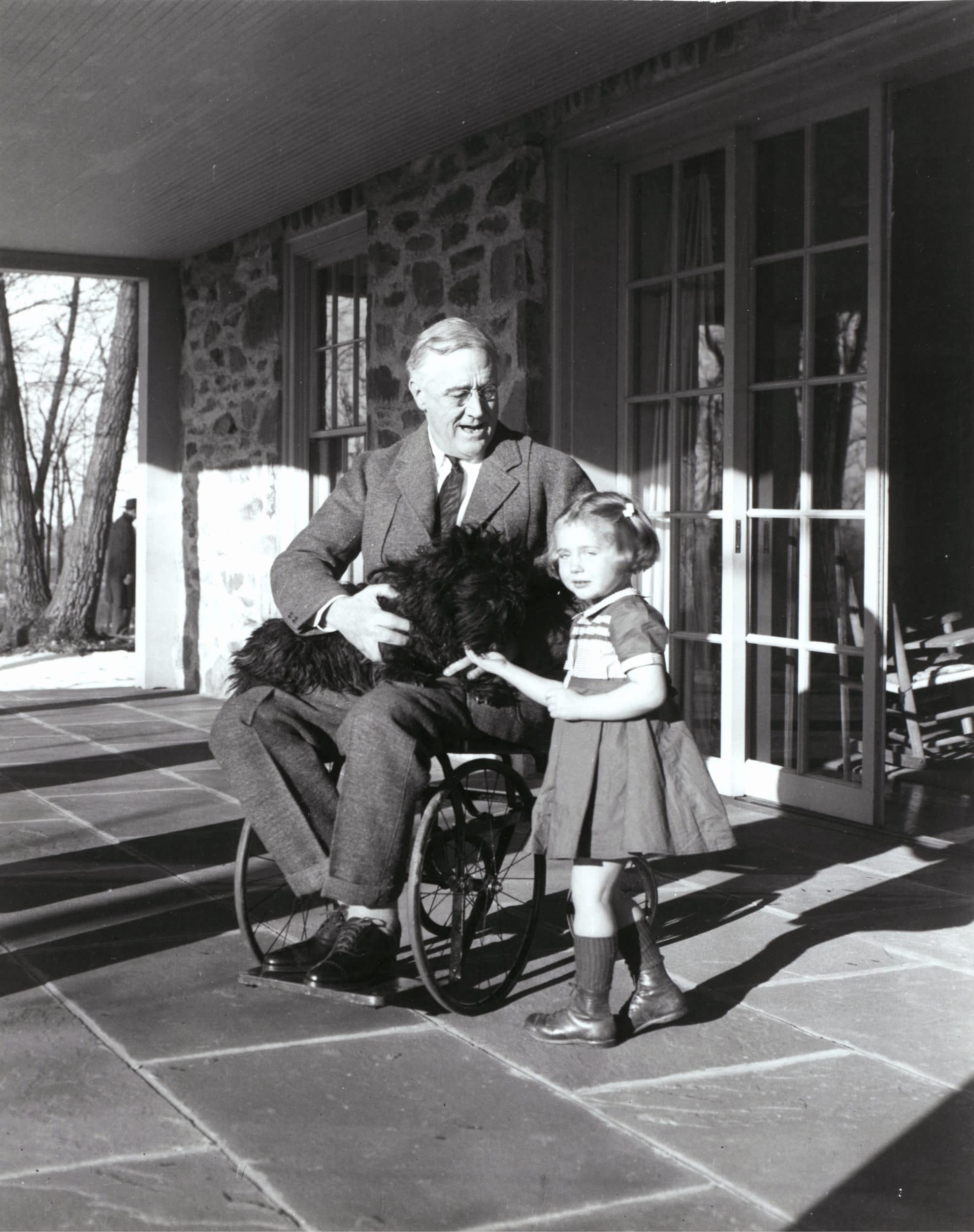 Photograph of FDR in a wheelchair with a young child.