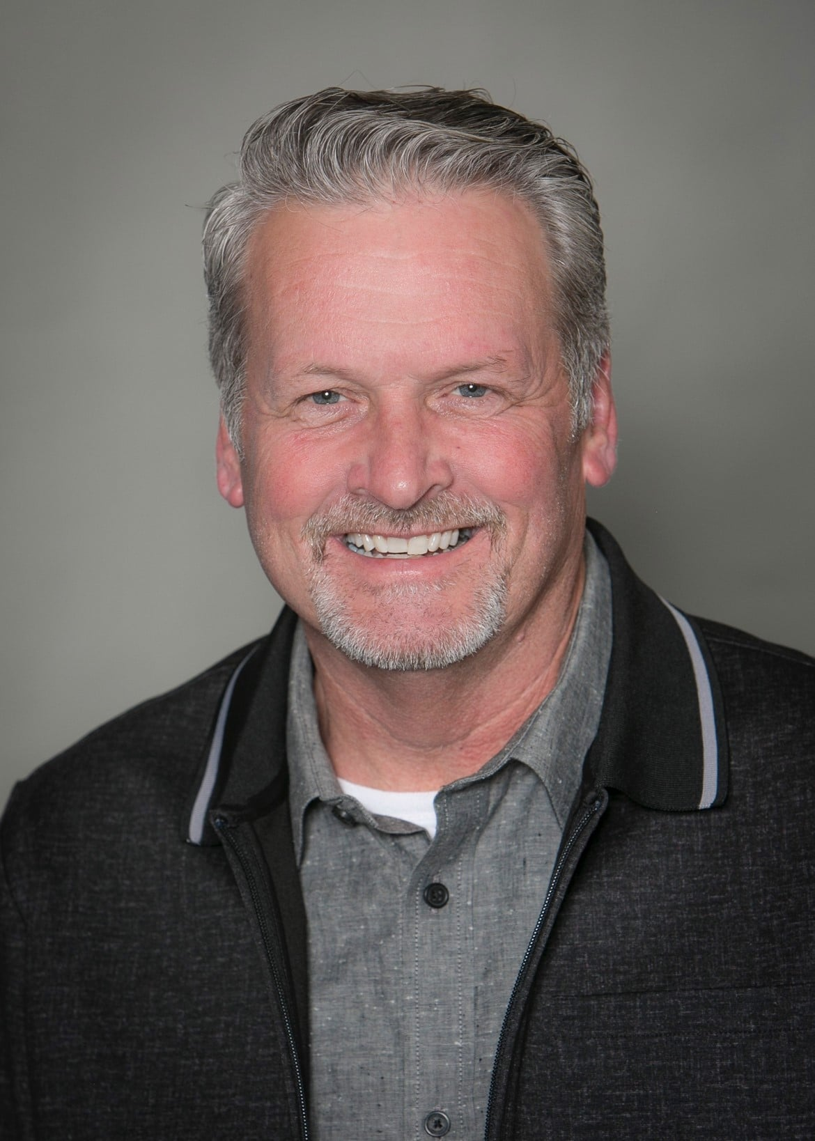 Headshot of Mark Balsano wearing gray collared shirt under windbreaker