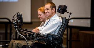 Student in a motorized wheel chair smilling