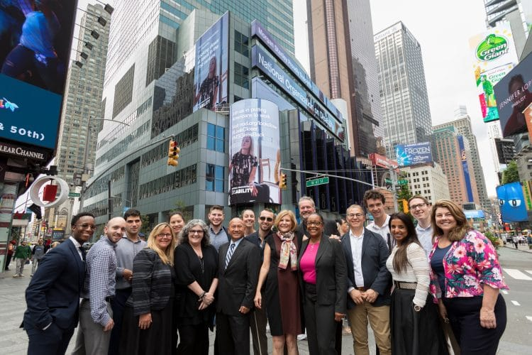 NOD + Morgan Stanley staff posed in front of Look Closer on digital billboards in Times Square