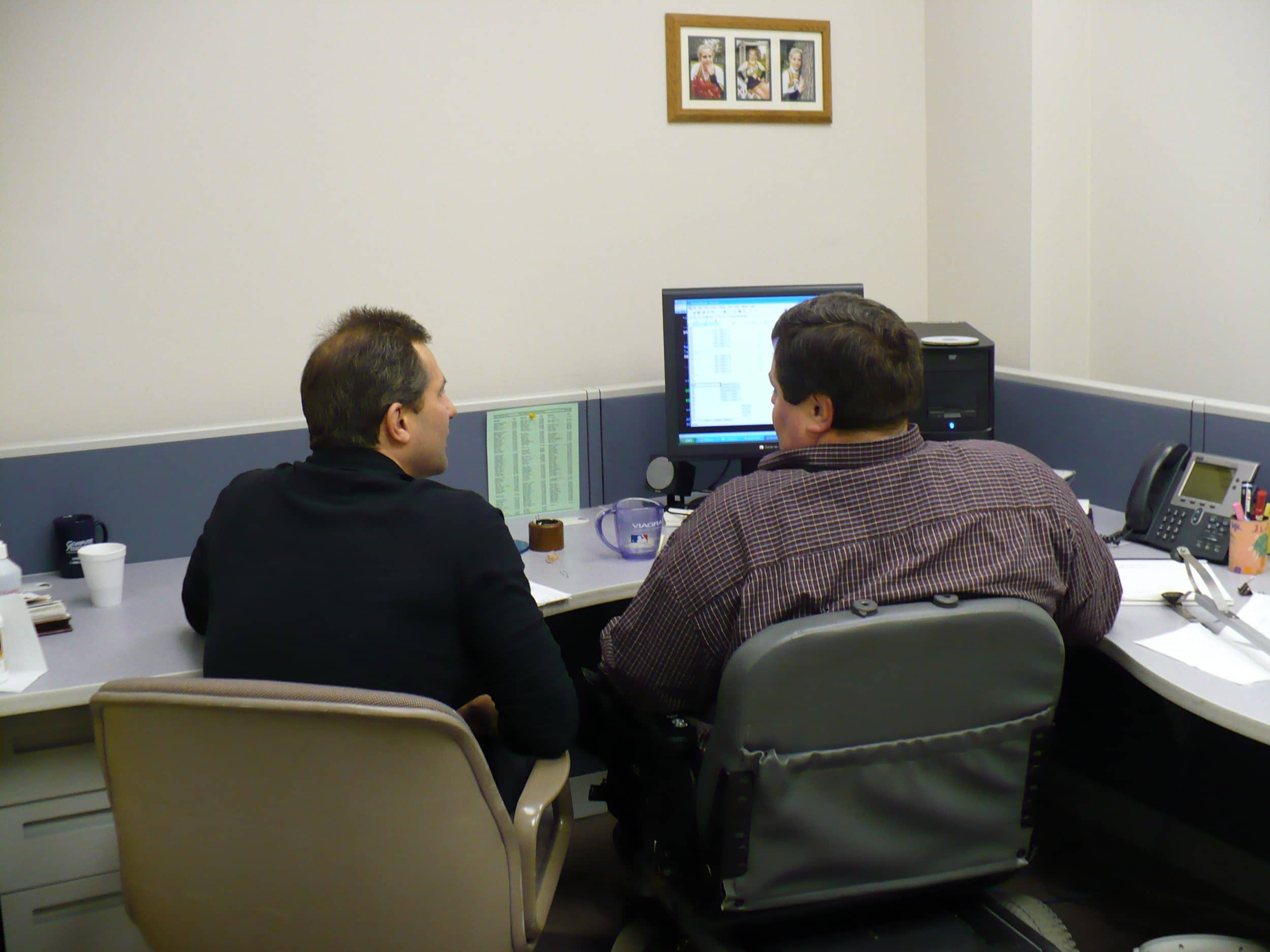 Two men siting at a desk with a computer photographed from behind.
