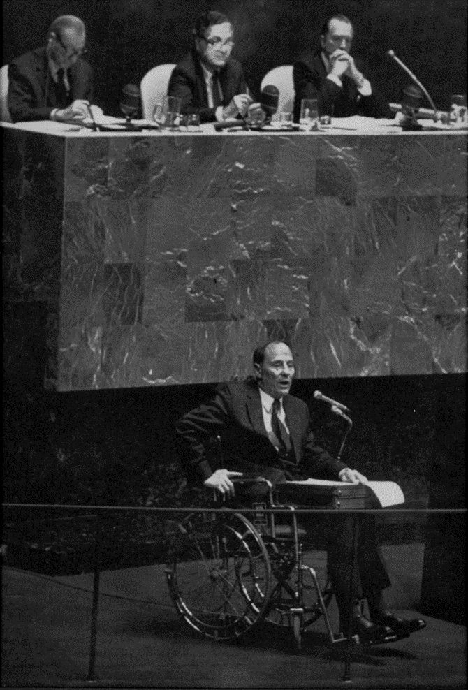 Black and white photo of Reich, in wheelchair, speaking at UN, while three men look down at him from elevated podium.