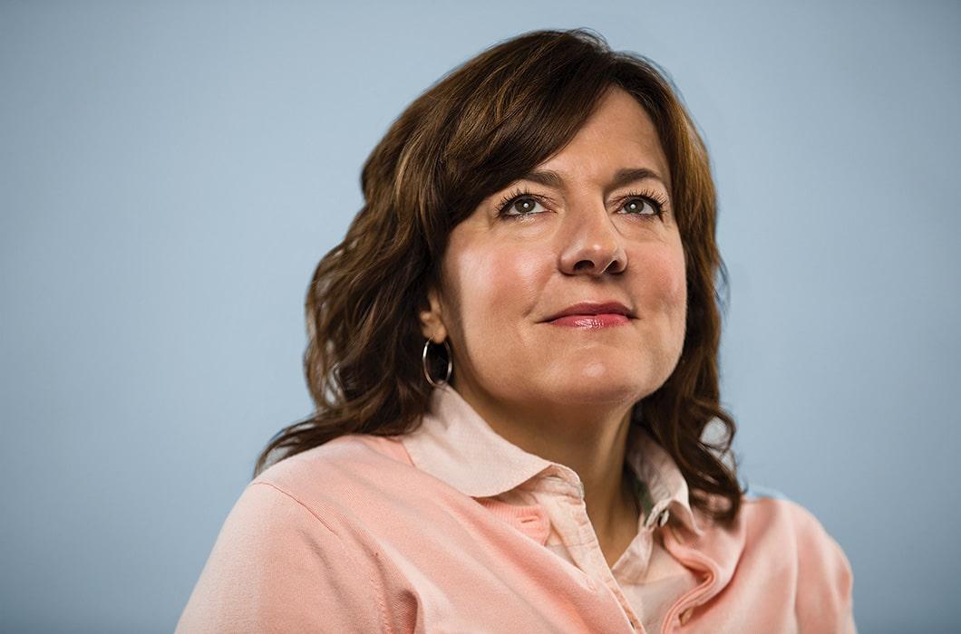 Headshot of Ann Rembach on blue background