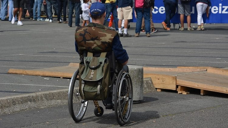 Man in camouflage jacket, using wheelchair in a parking lot, looking on a group of standing people.