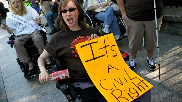 "Protestors in wheelchairs at an outdoor rally. Woman holds sign reading ""It's a Civil Right"""