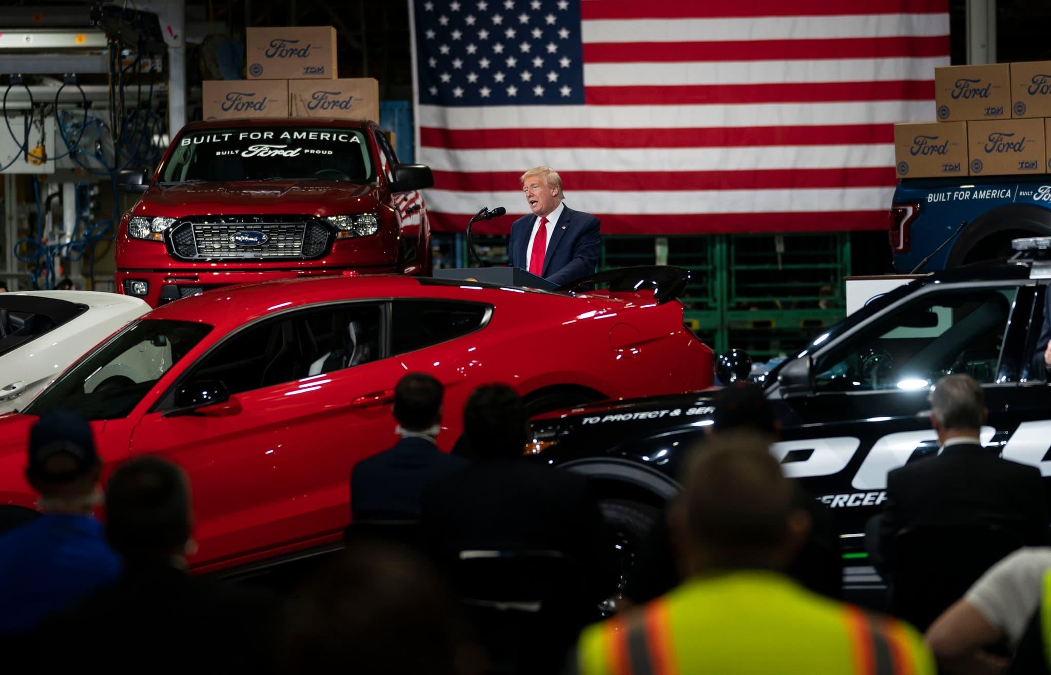 Donald Trump standing behind a sports car