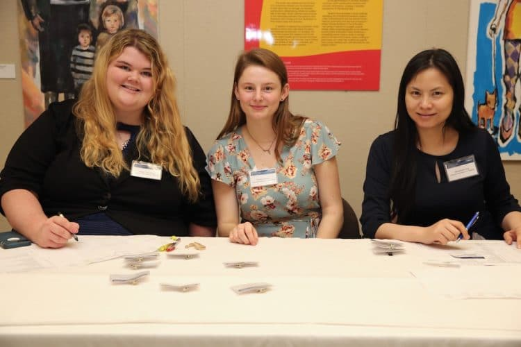 Kaitlin seated with two staffers at a NOD event