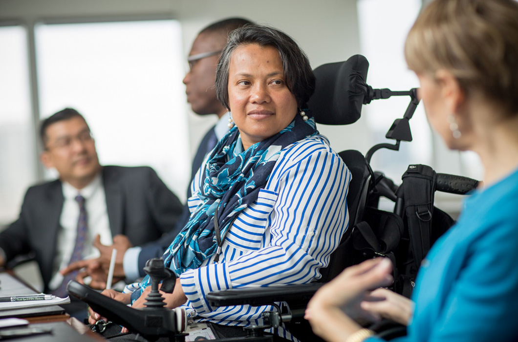 Suria Nordin in her wheelchair, smiling and talking with coworkers