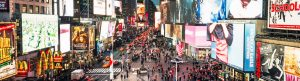 Photo of Times Square at night with many lights, advertisements, people and traffic, connoting a busy streetscape